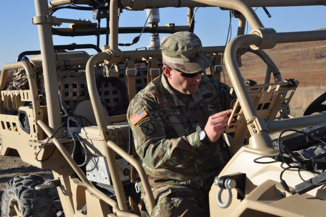 Sgt. Nathan Stivers, 2nd Combined Arms Battalion, 137th Infantry Regiment from Kansas, works on the Killer vehicle Dec. 11, at the Maneuver Fires Integrated Experiment on Fort Sill. The Killer's ability is to fight in the cyberspace battlefield, disrupting the communication between vehicle and operator. (Photo by Monica K. Guthrie)