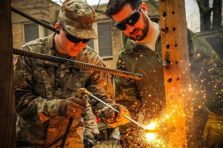 A paratrooper assigned to the 82nd Airborne Division cuts through steel rebar with the Silent Entry Torch System during new equipment training at the Muscatatuck Urban Training Complex, North Vernon, Ind., Feb. 22, 2017.