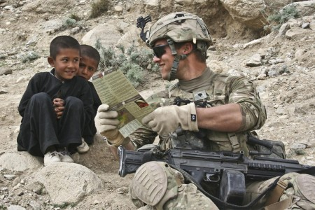 A squad automatic weapon gunner with 34th Infantry Division, reads some Dari phrases to two curious young Afghan boys in the Galuch Valley, Afghanistan, March 27, during Operation Promethium Puma.