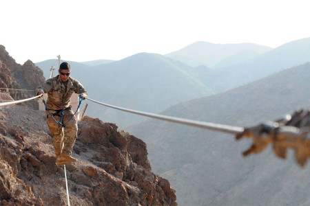 A Soldier assigned to 39th Infantry Brigade Combat Team, walks across the wire during the mountain obstacle portion of the French Desert Commando course in Djibouti, Africa, April 8, 2017.