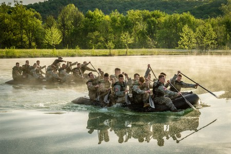 Two-man teams competing in the Best Sapper Competition were randomly placed into squads of 10 to carry 350 pound Zodiac boats to the lake at Fort Leonard Wood's Training Area 250. After paddling across the lake, squads were required to carry the Zodiacs to the Big Piney River and paddle downstream to the next event.