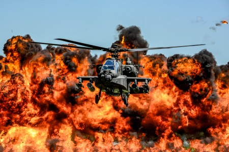 A U.S. Army AH-64D Apache Attack Helicopter flies in front of a wall of fire during the South Carolina National Guard Air and Ground Expo at McEntire Joint National Guard Base, S.C., May 6, 2017.