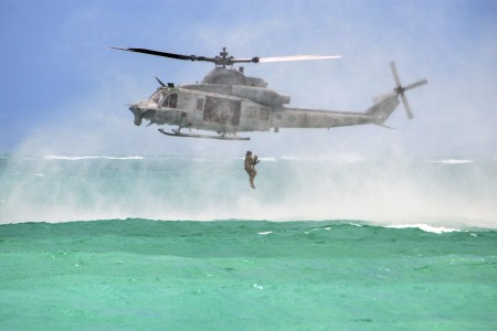 A Soldier jumps from a Marine Corps UH-1Y Huey helicopter into the Pacific Ocean near Marine Corps Training Area Bellows, Hawaii, May 16, 2017, during helocast insertion training.