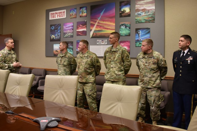 The five 100th Missile Defense Brigade (Ground-based Midcourse Defense) Soldiers who executed the intercept of a test intercontinental ballistic missile target May 30, 2017, are presented with coins of excellence by Lt. Gen. James Dickinson, left, commanding general, U.S. Army Space and Missile Defense Command/Army Forces Strategic Command, June 2, 2017, at SMDC headquarters in Colorado Springs. The flight test, dubbed Flight Test Ground-based Interceptor (FTG)-15, was the first successful intercept of an ICBM target by the GMD system. (Photo has been graphically manipulated to conceal Soldiers' names for security)