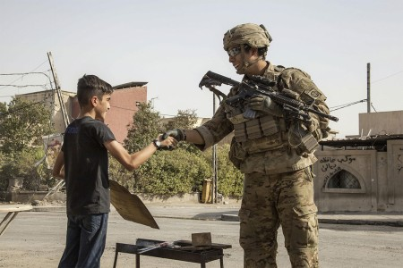 A Soldier shakes the hand of a young boy while patrolling to support Operation Inherent Resolve in Mosul, Iraq, July 4, 2017. The soldier is a paratrooper assigned to the 82nd Airborne Division's 2nd Brigade Combat Team.