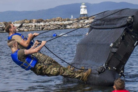 Vermont Army National Guard Soldiers with 86th Infantry Brigade Combat Team (Mountain), right a zodiac boat during boat capsizing training, Burlington, Vt., Aug. 12, 2017. They conducted water training for proficiency in water-based recon missions.