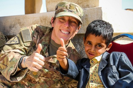 A Soldier with Civil Liaison Detachment Team 59, makes a new friend as she helps hand out school supplies and candy to children during a community engagement event near the King Abdullah II Special Operations Training Centre, Amman, Jordan, Aug. 18, 2017. The project was a cooperation between U.S. service members in Jordan and the Jordan Armed Forces -- Arab Army aimed at building strong relationships between the armed forces and local community members.