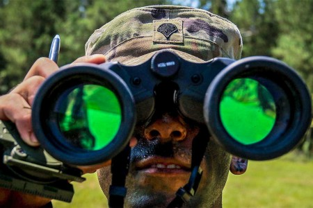 A human recourse specialist from 11th Armored Cavalry Regiment, looks through his binoculars as part of an orienteering event during second day of the 2017 Forces Command Best Warrior Competition at Fort Bragg, N.C., Aug. 21.