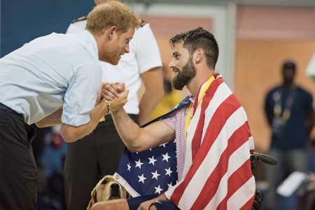 Prince Harry shakes hands with Army veteran Sgt. Stefan Leroy as his dog Knoxville looks on after a medal ceremony during swimming finals at the 2017 Invictus Games in Toronto Pan Am Centre, Sept. 29, 2017. The Invictus Games, established by Prince H...