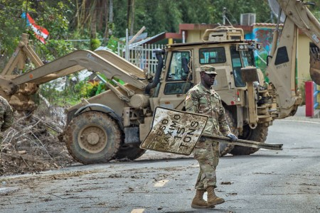 A South Carolina National Guard Soldier with Task Force Palmetto, helps clear a road in the vicinity of Cayey, Puerto Rico. The Soldiers are working in conjunction with the 190th Engineer Battalion of the Puerto Rico National Guard to clear mud and debris from the roads in the wake of Hurricane Maria and subsequent rain storms.