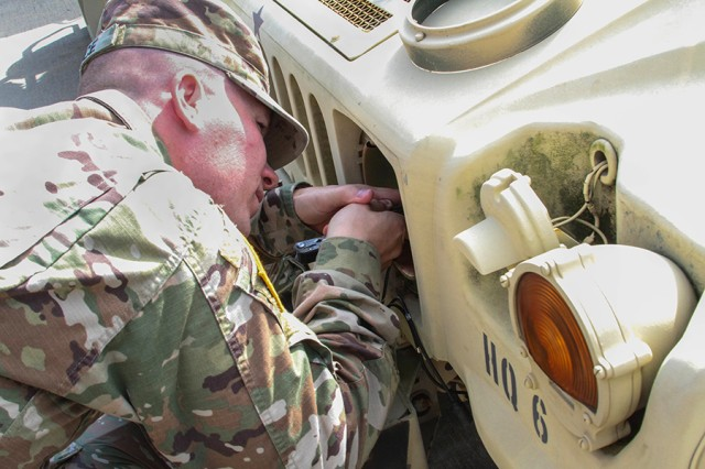 Sgt. Thomas Bruce, the 35th Theater Tactical Signal Brigade motor sergeant, helps with maintenance during his unit's biannual field training exercise at Fort Gordon, Ga., on Nov. 5, 2017.