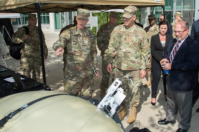 Maj. Gen. Randy S. Taylor, commander of the Communications-Electronics Command, discusses communications, computers, intelligence, surveillance, and reconnaissance sustainment challenges with Gen. Gustave Perna, commander of the Army Materiel Command, at Aberdeen Proving Ground, Md. The item in front of them is part of the transportable tactical command communications satellite terminal.