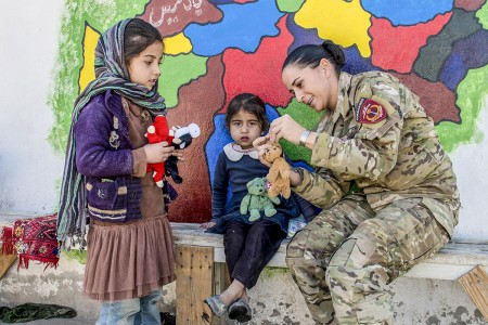 U.S. Army chief warrant officer, an Afghan National Army Special Operations Advisory Group mentor, assists with the Afghan Commandos' routine essential items distribution at the Camp Commando medical clinic, Kabul, Nov. 6, 2017. All items provided to the Afghan women and children are donated from local villages.