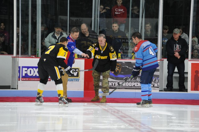 Maj. Gen. Walter E. Piatt joins Watertown Mayor Joseph Butler for the ceremonial puck drop during the exhibition game between the All-Army Ice Hockey Team and the Canadian Armed Forces Ice Hockey Team on Dec. 16 at Watertown Municipal Arena.