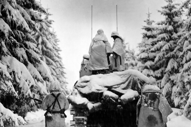 Battle of the Bulge tanks and infantrymen of the Company G, 740th Tank Battalion, 504th Regiment, 82nd Airborne Division, push through the snow toward their objective near Herresbach, Belgium on Jan. 28, 1945.