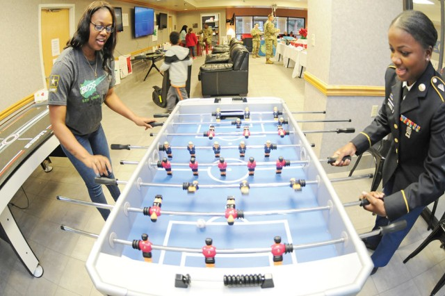Pvt. 1st Class Shyyandria Walker, VETCOM, plays a game of foosball with Spc. Mykea Carroll, A Co., 1-145th Avn. Regt., at the newly renovated BOSS building Dec. 13.