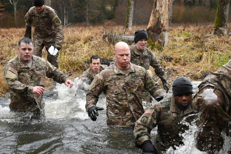Senior leaders with the 18th Military Police Brigade cross a creek during the brigade's first senior leader physical challenge at the 7th Army Training Command's Grafenwoehr Training Area, Germany, Nov. 28, 2017. The purpose of the senior leader physical challenge is to execute a team building training session which includes a series of physical and mentally demanding obstacles.