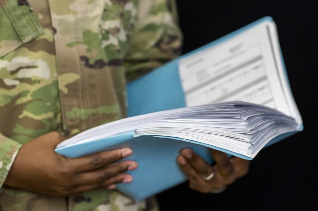Chief Warrant Officer 4 Joseph Dean, senior property accountability technician, Distribution Integration Division, U.S. Army Sustainment Command, displays a small portion of the documents he accumulated while providing logistical support to the 1st Security Force Assistance Brigade, Fort Benning, Georgia. (Photo by Kevin Fleming, ASC Public Affairs)