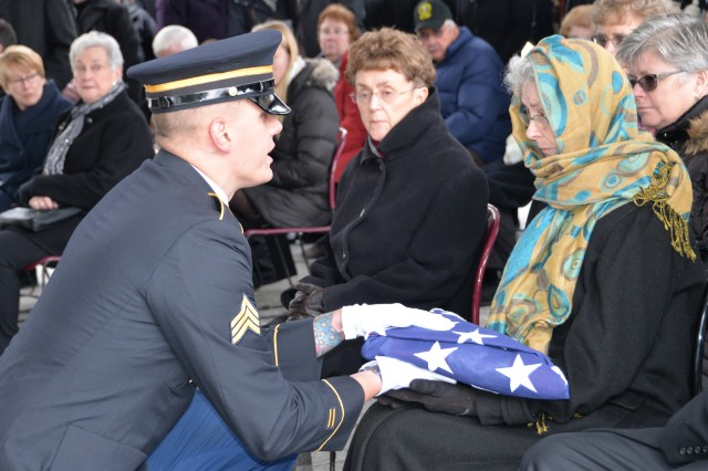 New York Army National Guard Sgt. Nicklaus Hilts, presents a U.S. Flag to a family member of Army Veteran 1st Lt. Lawrence Ostwald during his burial at Gerald B.H. Solomon Saratoga National Cemetery, in Schuylerville, N.Y. on December 15, 2017. Ostwald served in the U.S. Army from 1951-54.