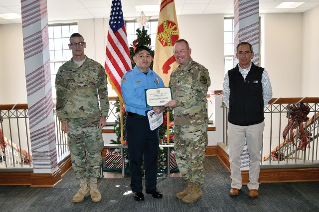 Sgt. Johnny Cornejo of the Directorate of Emergency Services receives his Employee of the Month October award from Col. John D. Lawrence, Fort Riley garrison commander, Dec. 15 at garrison headquarters. At left is the Fort Riley garrison's senior noncommissioned officer Command Sgt. Maj. James Collins. At right is deputy garrison commander Tim Livsey.