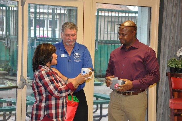 Eileen Catalan DeLa Cruz, manager at the 3 Star Recreation Center in Brussels, and David Coldwell, business and recreation chief for Family and Morale, Welfare and Recreation, give presents to Derrick Hood, former deputy garrison manager for USAG Benelux in Brussels, Dec. 15, 2017, in Brussels.