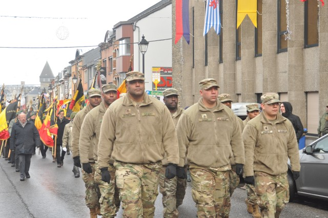 The USAG Benelux formation walks by the city hall of Bastogne during the Battle of the Bulge's 73rd Anniversary parade in Bastogne, Dec. 16, 2017.