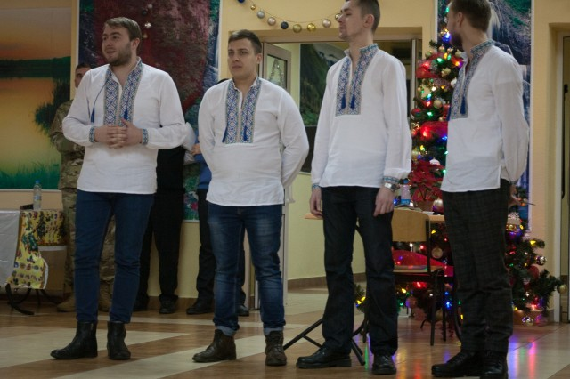 Yavoriv, Ukraine - A Ukrainian quartet performs a selection of traditional Ukrainian Christmas Carol during a Christmas dinner at the Yavoriv Combat Training Center near Yavoriv, Ukraine. Currently more than 220 New York Army National Guard Soldiers are deployed to Ukraine and spent the holidays more than 4500 miles from home.