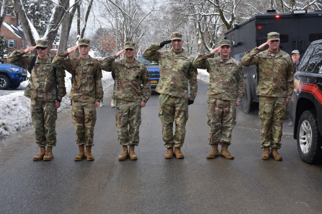 N.Y. Army National Guard Soldiers assigned to Recruiting and Retention Command, Bravo Company, salute the American Flag during the Christmas Eve Road March, Glens Fall, N.Y., Dec. 24, 2017. Soldiers and families of service members participated in Sgt. First Class (retired) Arthur Coon's Christmas Eve Road March to honor men and women currently deployed, who cannot celebrate the holidays with their families.