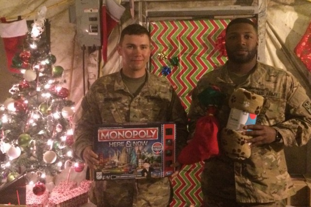 """Cpl. Paul George (Left) and Pfc. Brandon Matthews (right), both assigned to Bravo Battery, 2nd Battalion, 43rd Air Defense Artillery """"Warriors"""" Regiment, 11th Air Defense Artillery Brigade, show off some of the presents Dec. 18, 2017, that they received from care packages given to the battery. (U.S. Army photo by 1st Lt. Shaun Bruner, 2-43 ADA UPAR)"""
