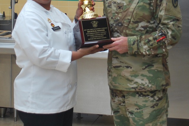 Colonel Peter Crandall, commander, 404th Army Field Support Brigade, presents the trophy for winning the FY18 Philip A. Connelly Regional Award in the Garrison Dining Facility Category to Master Sgt. Candice Williamson, senior brigade culinary management non-commissioned officer, 16th Combat Aviation Brigade, 7th Infantry Division, during a ceremony Dec. 11 at the Raptors' Nest Dining Facility, Joint Base Lewis-McChord, Washington.