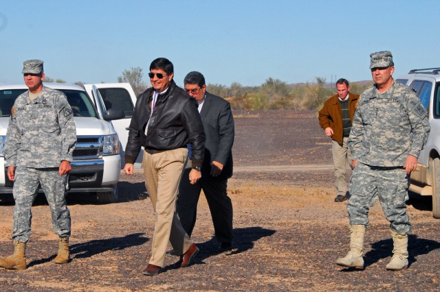Retiring U.S. Army Yuma Proving Ground (YPG) Technical Director Julio Dominguez (second from left) escorts then-Vice Chief of Staff of the Army Gen. Peter Chiarelli (right) on a tour of a YPG gun position in this 2011 photo. That year, the YPG workforce gave a record 2.8 million direct labor hours to testing equipment for the Warfighter.