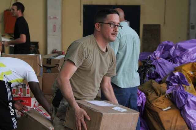 Sgt. John Marshall, Task Force Darby mail clerk at Contingency Location Garoua, Cameroon, helps to sort a record number of packages Dec. 20. TF Darby soldiers are serving in a support role for the Cameroon military's fight against the violent extremist organization Boko Haram. (Photo by Staff Sgt. Christina J. Turnipseed, Contingency Location Garoua Public Affairs)