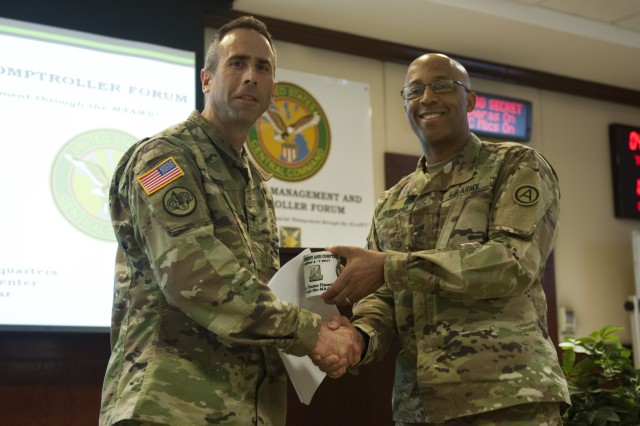 Colonel Brian Smith receives a token of appreciation from Brig. Gen. Kenneth Hubbard, U.S. Army Central senior financial manager, after speaking at the 2018 Financial Management and Comptroller Forum, Dec. 4, 2017 in Qatar. The forum provided an opportunity for leaders to meet and discuss ways to better use military resources. (U.S. Army photo by Spc. Joseph Black, USARCENT PAO)