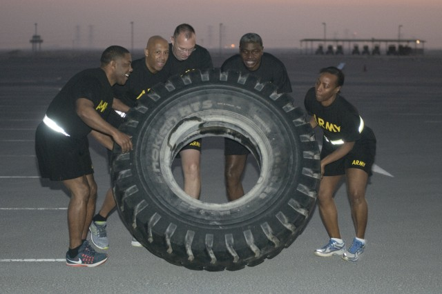 Sergeant 1st Class Tyrone Griffin, Brig. Gen. Kenneth Hubbard, Col. Cody Zilhaver, Sgt. Maj. Herlitz Henderson and Lt. Col. Leah Jones participate in a team-building fitness competition as part of the Financial Management and Comptroller Forum, Dec. 6, 2017 in Qatar. The competition included many complex physical trials including a buddy carry, tire flip, litter carry and more, all requiring participants to work together to complete the given task. (U.S. Army photo by Spc. Joseph Black, USARCENT PAO)