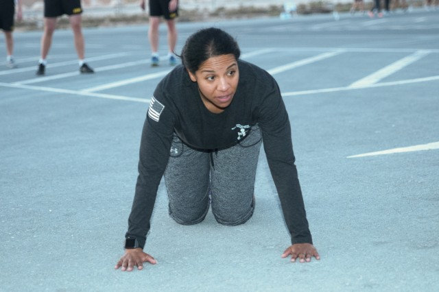 Staff Sgt. Pamela Thomas prepares to complete a pushup event during a team-building fitness competition as part of the Financial Management and Comptroller Forum Dec. 6, 2017 in Qatar. The competition included physical challenges like buddy carries, tire flips, litter carries and more, all requiring participants to work together to complete the given task. (U.S. Army photo by Spc. Joseph Black, USARCENT PAO)
