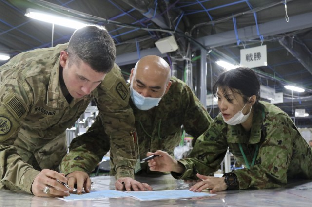 Maj. Christopher Wagener, an intelligence officer with 17th Field Artillery Brigade, works with a Japanese counterpart and an interpreter to identify locations on a map of Japan during Yama Sakura 73, Camp Sendai, Japan, Dec. 7, 2017. Yama Sakura 73 is a command post exercise between the U.S. Military and the Japan Self-Defense Forces, Dec. 1-12, 2017(U.S. Army Photo by Sgt. Jacob Kohrs)
