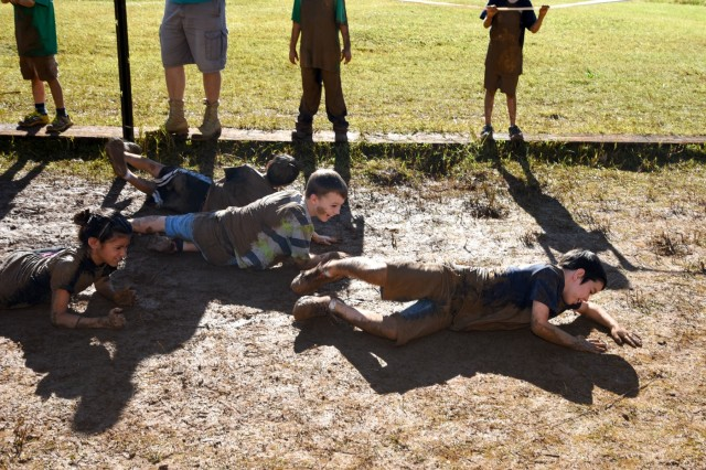 Cub Scouts from across Oahu low crawl through a mud pit during Schofield Days on Schofield Barracks, Hawaii, December 27, 2017. Schofield Days is an Army community relations event where Soldiers conduct, teach and share techniques they use on a daily basis to serve and protect the nation. (U.S. Army photo by Staff Sgt. David N. Beckstrom, 2nd Infantry Brigade Combat Team, 25th Infantry Division)