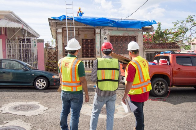 Andrew Lorenz (right), a Quality Assurance specialist with the U.S. Army Corps of Engineers, works with contractors to make a material adjustment at a home receiving a temporary blue roof in Mayagüez, Puerto Rico Dec. 30.