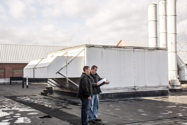 Scott Evertsen, the Arsenal's energy manager, left, discussing with contract representative Michael White about the scope of the contract that will improve energy use by the large heating and ventilating units in the background.