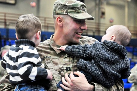 Cpt. Sebastiano Nane of the 548th Combat Sustainment Support Battalion holds his sons after a redeployment ceremony at Fort Drum's Magrath gym, Dec. 18. Nane held one of his sons for the first time that night.