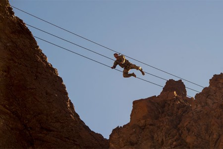 A Soldier assigned to Combined Joint Task Force - Horn of Africa, crawls across suspended wires during the mountain obstacle portion of the French Desert Commando Course held at Arta, Djibouti, Dec. 3, 2017. Thirty U.S. service members participated in the obstacle course alongside French marines assigned to the 5th Overseas Interarms Regiment, Djibouti.