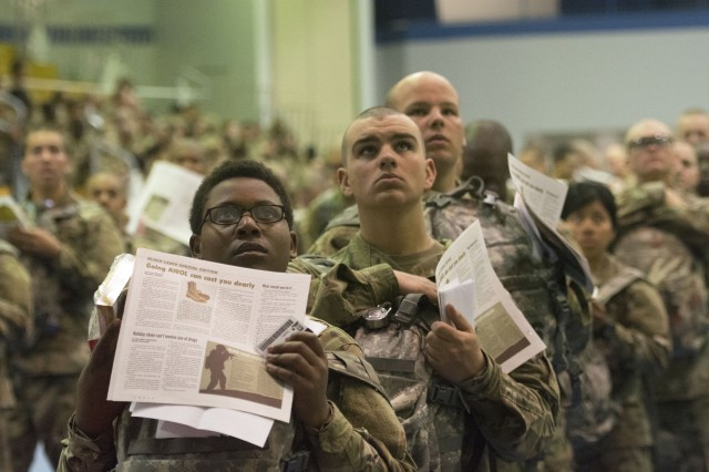 Trainees look up at the news as its played on big screen while they stand in line during processing at the Solomon Center on Fort Jackson Dec. 18 a for departure on Victory Block Leave. Roughly 6,000 trainees from Fort Jackson will be traveling home for the holidays before coming back to their post to continue training. The trainees hold copies of a special insert from the Fort Jackson Leader that details what to expect on Victory Block Leave.