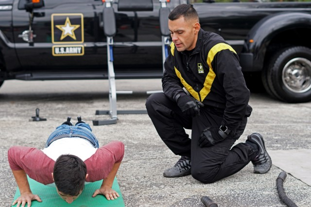 Staff Sgt. Frank Keffales, an exhibitor with the Mobile Exhibit Company, Fort Knox, Kentucky, counts pushups for a student at the GoArmy Experience Zone during the 2018 U.S. Army All-American Bowl week outside of the Alamodome in San Antonio, Texas, Jan. 5, 2018. The Army Experience Zone demonstrates the Army's commitment to America's youth by showcasing different aspects in Army life.