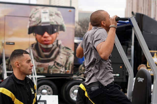 Staff Sgt. Frank Keffales, an exhibitor with the Mobile Exhibit Company, Fort Knox, Kentucky, counts pull ups for a student at the GoArmy Experience Zone during the 2018 U.S. Army All-American Bowl week outside of the Alamodome in San Antonio, Texas, Jan. 5, 2018. The Army Experience Zone demonstrates the Army's commitment to America's youth by showcasing different aspects in Army life.