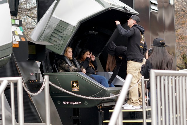 Students climb in to a flight simulator at the GoArmy Experience Zone outside of the Alamodome in San Antonio, Texas, during the 2018 U.S. Army All-American Bowl Week, Jan. 5, 2018. The Army Experience Zone demonstrates the Army's commitment to America's youth by showcasing different aspects in Army life.