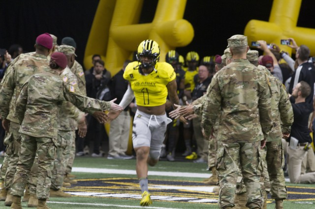 Jaiden Woodbey, an athlete from St. John Boscoe High School in Bellflower, Calif., runs out onto the field during the pre-game events at the U.S. Army All-American Bowl Jan. 6, 2018, in San Antonio, Texas. The All-American Bowl is the nation's premier high school football game, serving as the preeminent launching pad for America's future college and National Football League stars. (U.S. Army photo by Sgt. Ian Valley, 345th Public Affairs Detachment/Released)