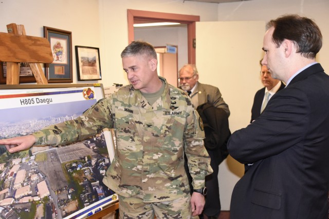 Col. Robert P. Mann Jr. briefs William J. Gillis on the Area IV Southern Hub Development Plan. The plan addresses readiness gaps in capacity and in aged infrastructure. The recently finished project is the construction of the Daegu Middle High School completed on Camp Walker, last August.