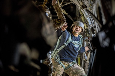 U.S. Army Staff Sgt. Nikita Revilloza, a jumpmaster with the 112th Signal Battalion (Special Operations)(Airborne), relays commands during the 20th Annual Randy Oler Memorial Operation Toy Drop at Camp MacKall, N.C., Dec. 4, 2017. Eight countries participated, including Colombia, Canada, Latvia, the Netherlands, Sweden, Italy, Germany, and Poland. Operation Toy Drop, hosted by the U.S. Army Civil Affairs & Psychological Operations Command (Airborne) is the largest combined airborne operation conducted worldwide.