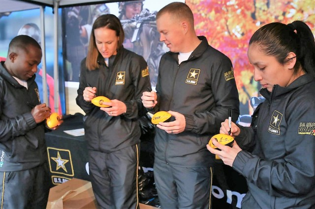 WCAP athletes autograph footballs to give away at the Go Army Experience: (from left) Staff Sgt. Spenser Mango, Sgt. Shauna Rohbock, Staff Sgt. Dennis Bowsher and 1st Lt. Selina Bocanegra.