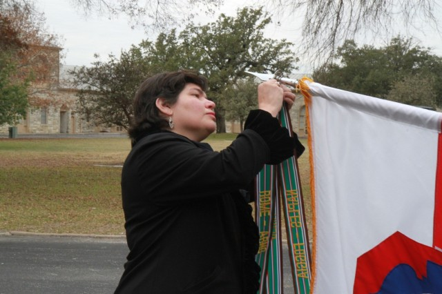 "Andrea Gastaldo, the foreign Policy Advisor to U.S. Army North, places the Rome-Arno campaign streamer on the unit's colors Jan. 5 during the 75th Anniversary of Fifth Army inside the historic Quadrangle at Fort Sam Houston. Andrea is the daughter of Maj. Edward ""Eddie"" Gastaldo, an Italian-American who fought behind enemy lines as an intelligence officer for Fifth Army headquarters during the Italian Campaign in WWII. (Photo by Staff Sgt. Tomora Nance, U.S. Army North Public Affairs)"